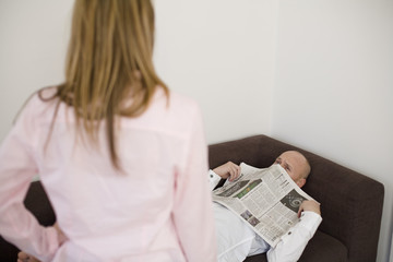 Woman standing while man lying with newspaper on face