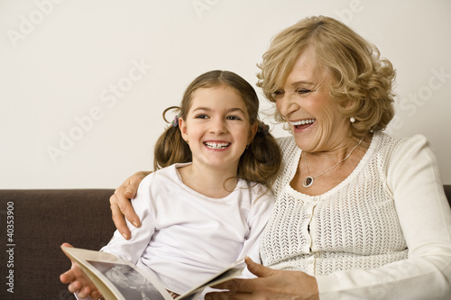 Senior woman with granddaughter holding photograph album