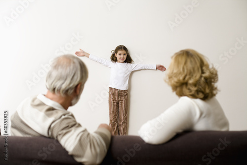 Senior man and woman sitting on sofa while girl standing by wall