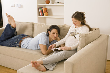Pregnant woman sitting on sofa with husband