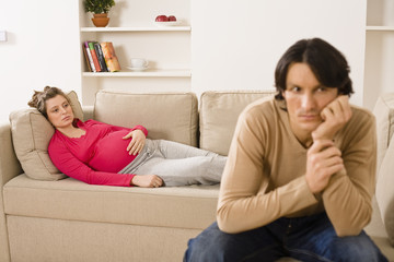 Man and pregnant woman in living room looking worried