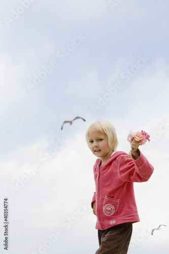 Girl holding flower and smiling