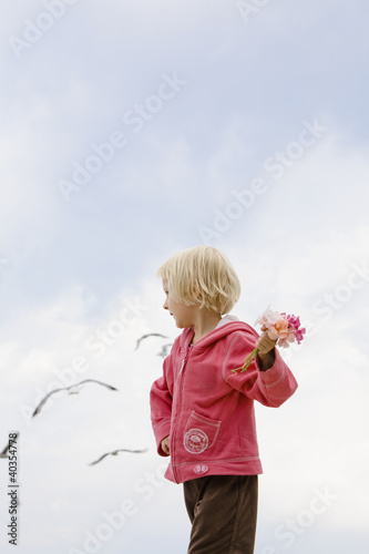 Girl holding flower and looking away