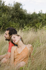 Mid adult couple sitting on grass