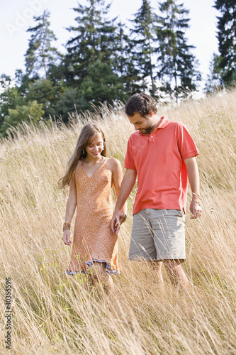 Mid adult couple standing in field, holding hands