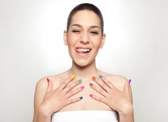 Junge Frau zeigt ihre farbigen Nägel