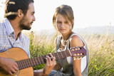 Mid adult couple in field with guitar