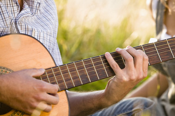 Mid adult man playing guitar, close-up