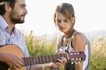 Mid adult couple sitting on field, man playing guitar
