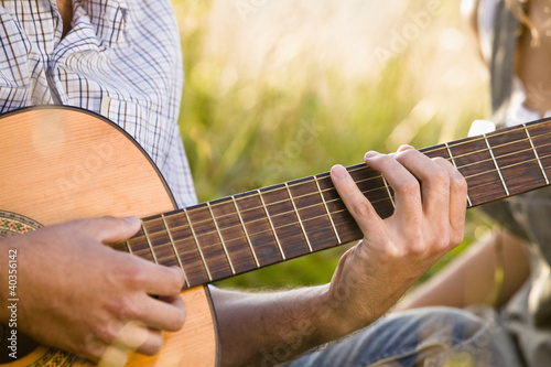 Mid adult man playing guitar, close-up