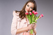 young brunette woman in pink coat holding flowers