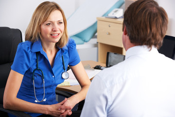 Female UK doctor talking to male patient