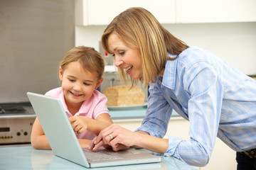 Mother and daughter using laptop in domestic kitchen