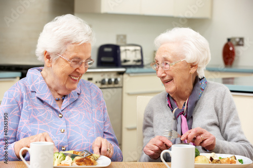 canvas print picture Senior women enjoying meal together at home