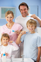 Family cleaning teeth together in bathroom