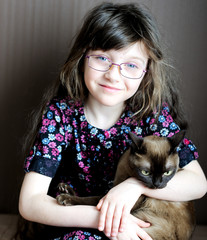 Portrait of little girl holding burmese cat
