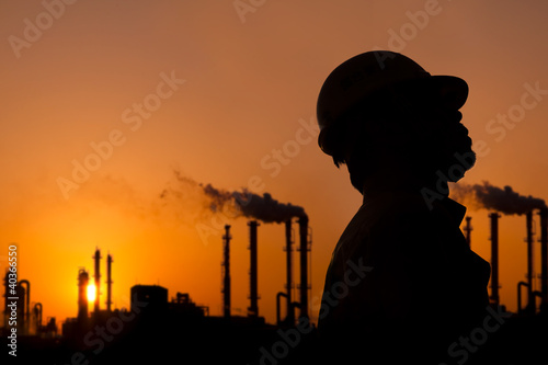the silhouette of oil refinery worker at sunset