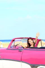 Woman driving convertible car waving happy