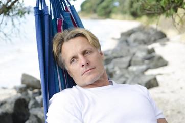 pensive man laying in hammock