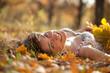woman lies in oak leaves