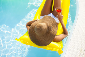 Young woman relaxing on pool with drink