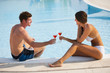 Happy couple enjoying thei drink by the pool