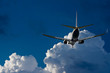 Passenger jet landing against a blue sky with white fluffy cloud