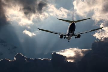 Passenger jet landing against a stormy sky