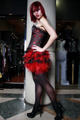 Beautiful redhead model wearing a red corset