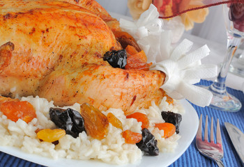 A fragment of grilled chicken with rice and dried fruit