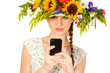 Beautiful girl with hat of flowers and phone in her hands