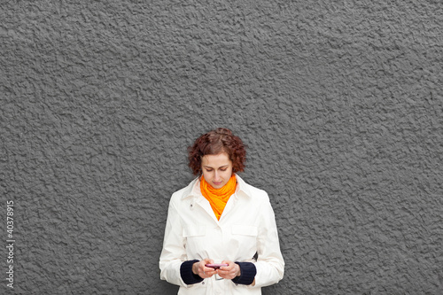Frau an Mauer mit Smartphone