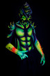 Man with fluorescent bodyart. Black background