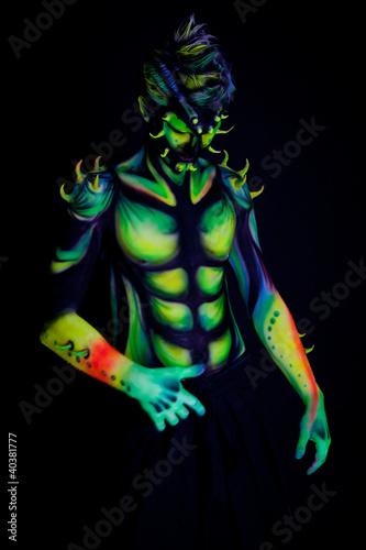 Man with fluorescent bodyart. Black background