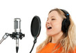Girl in headphones singing with studio microphone