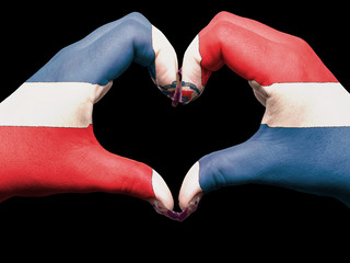 Heart and love gesture by hands colored in dominican flag for to