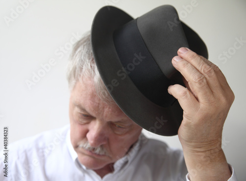 an older man puts on a fedora
