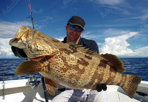 Happy  fisherman holding a grouper - 40390730