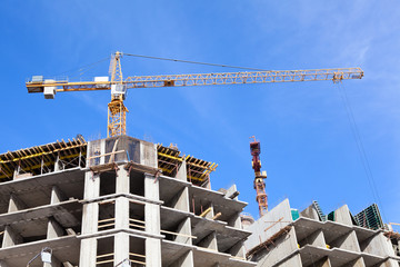 Buildings under construction with cranes on blue sky