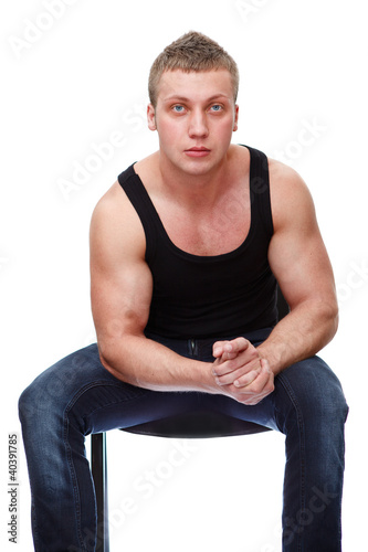 Muscle man in black t-shirt sitting on chair isolated on white