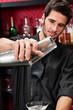 Young bartender make cocktail shaking drinks