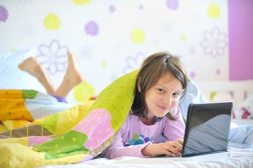 Teen girl in her bed looking on laptop