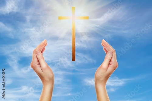 hands praying with a wooden cross
