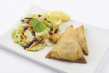 Samosas served with salad and lemon slices
