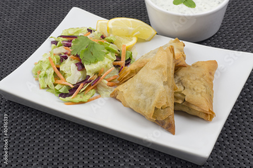 Samosas served with mint raita salad and lemon slices