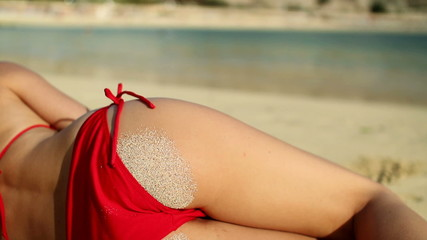 Sexy woman body in red bikini lying on the beach