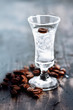 Tall glass with clear drink and coffee beans