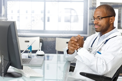 Troubled doctor sitting at desk