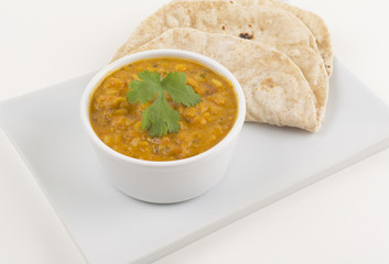 Tarka daal and chapati on a white background