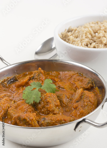 Indian Meat Madras served with pilau rice on a white background